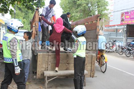AMAN - Petugas saat membantu warga naik angkutan darurat di simpang 4 bakso urip Kebumen